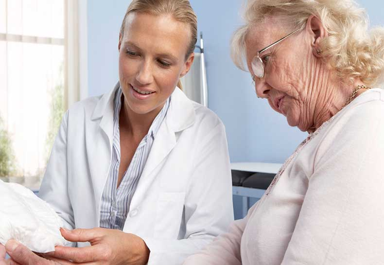 A doctor shows a lady a urinary incontinence product
