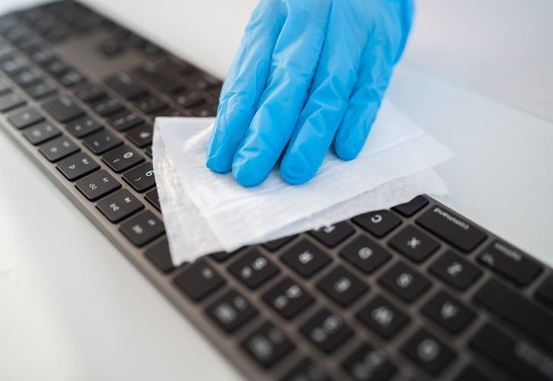 cleaning a keyboard with disinfecting wipes